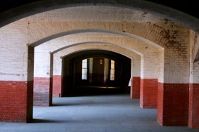 "Interior of Fort Point during International Orange. Artist Cornelia Parker's ""Reveille"" can be seen at the end of the corridor. Photo by John Cary."