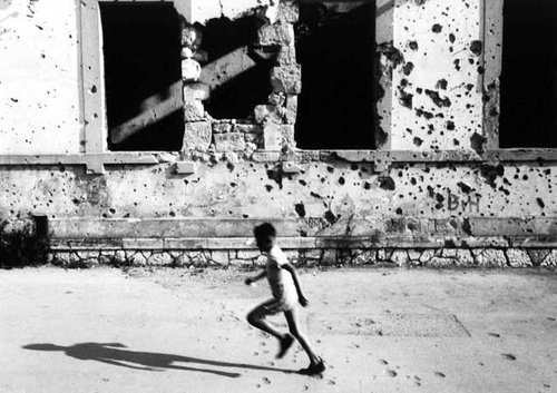 Child running home in the destroyed city of Mostar, Bosnia-Herzegovina in the hot summer of 1995. Photo by Thom Hoffman.
